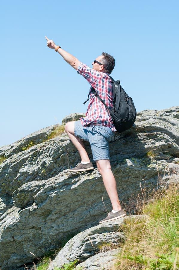 在摆在英雄射击的峭壁顶部的背包徒步旅行者 免版税库存照片