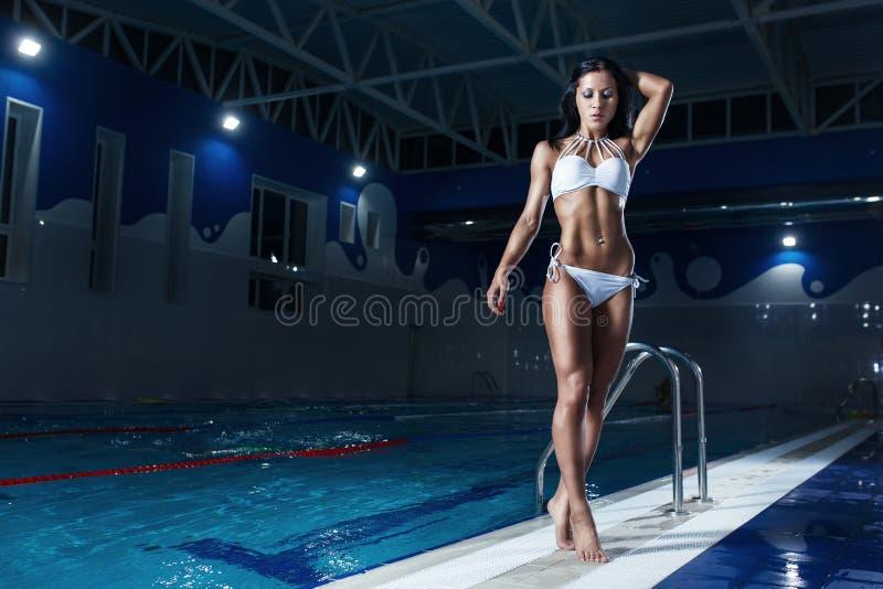在摆在水池的比基尼泳装的性感的深色的模型 库存照片