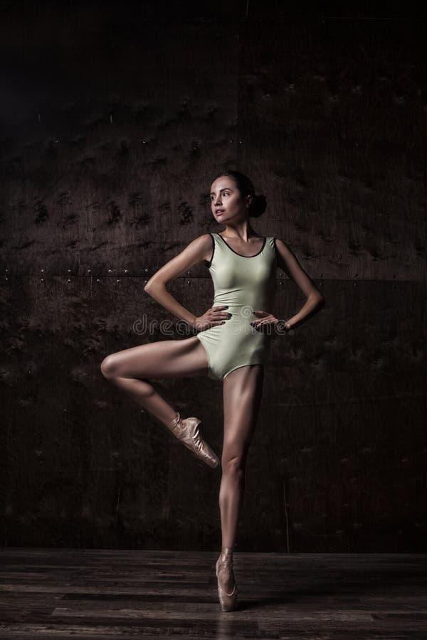 在摆在pointes的绿色泳装的年轻美丽的跳芭蕾舞者 库存照片