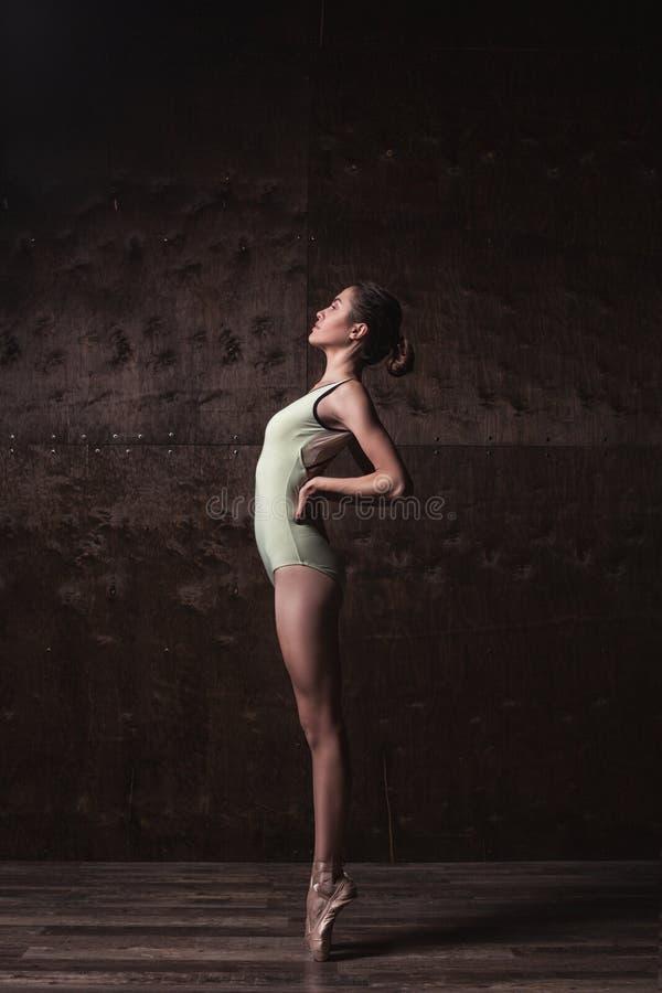 在摆在pointes的绿色泳装的年轻美丽的跳芭蕾舞者 免版税库存图片