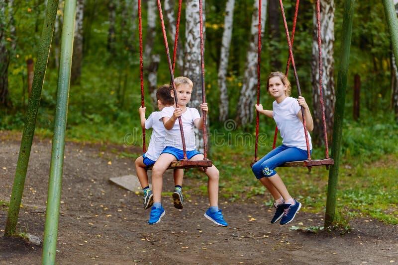 在摇摆的儿童游戏在夏天 免版税库存照片
