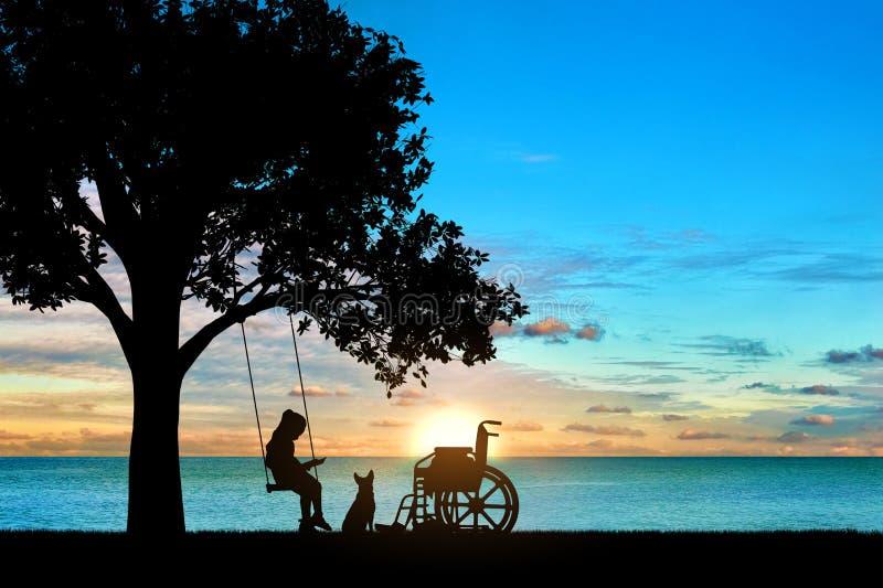 在摇摆的女孩女小学生无效开会在海的一棵树下,读书一本书,在轮椅和她的狗旁边 库存图片