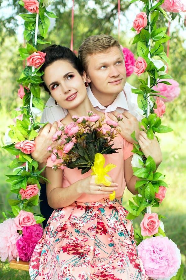在摇摆的愉快的年轻夫妇骑马 库存图片