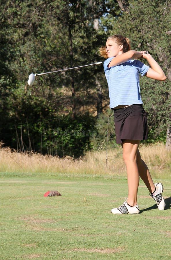 在摇摆以后的女性青少年的高尔夫球运动员 免版税库存照片