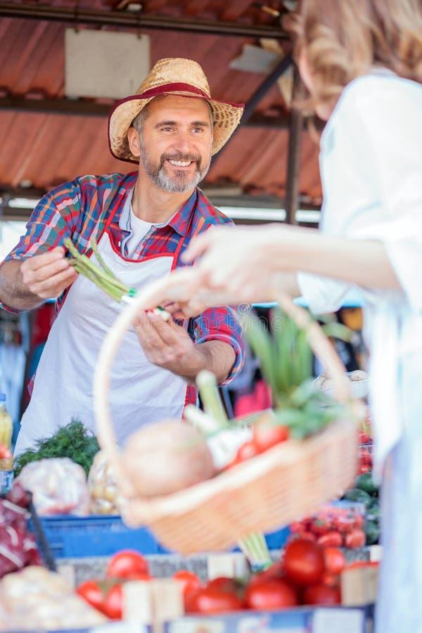 在摊位后的愉快的资深农夫身分,卖有机蔬菜在市场 免版税库存图片