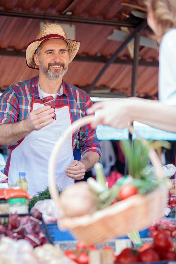在摊位后的愉快的资深农夫身分,卖有机蔬菜 免版税图库摄影