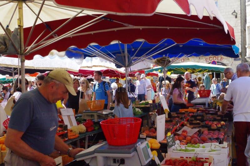 在摊位的人买的菜在市场上 库存图片