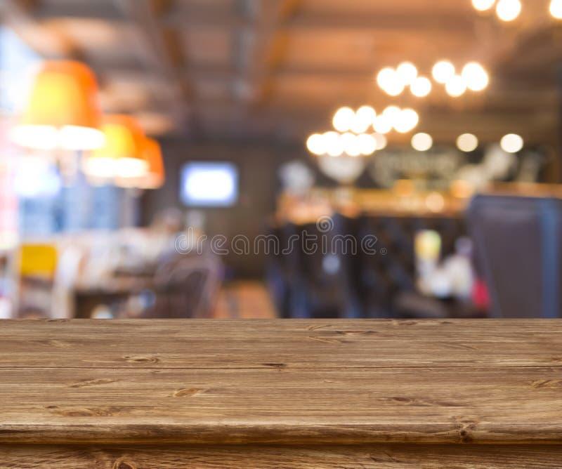 在摘要前面的木桌弄脏了resturant光背景 免版税图库摄影