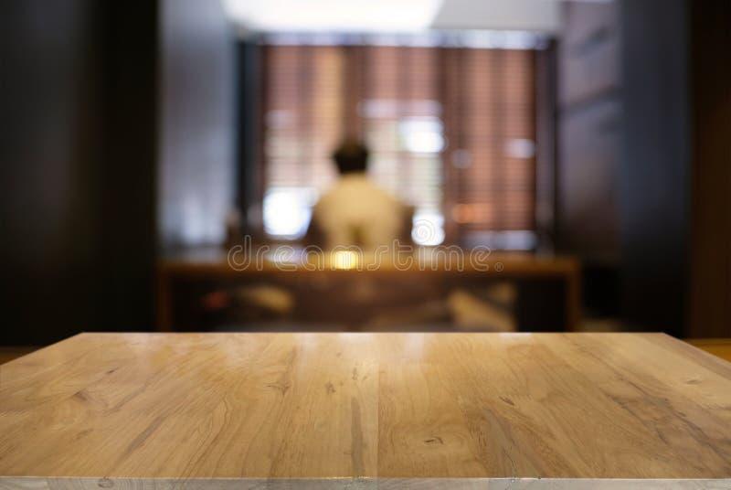在摘要前面的空的黑暗的木桌弄脏了bokeh backg 免版税库存照片