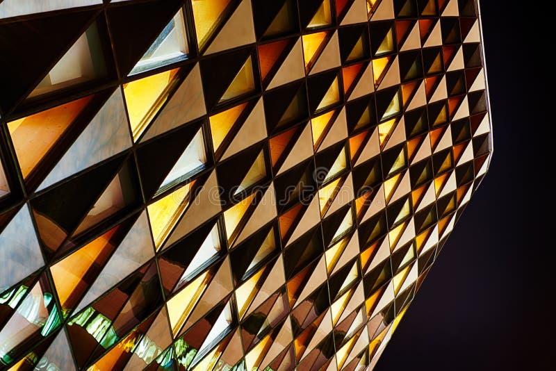 在摘要的办公室玻璃大厦在晚上 库存图片