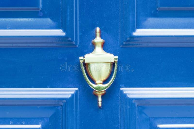 在摘要色的木门的老古色古香的金黄黄铜敲门人敲的关闭的  免版税库存图片