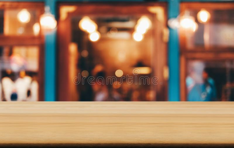 在摘要被弄脏的欢乐背景前面的选择聚焦空的木桌与夜市产品的背景bokeh 免版税库存图片