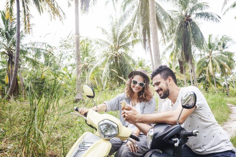 在摩托车的有吸引力的年轻夫妇在密林寻找在地图的一个方式在智能手机,在热带的蜜月 库存照片