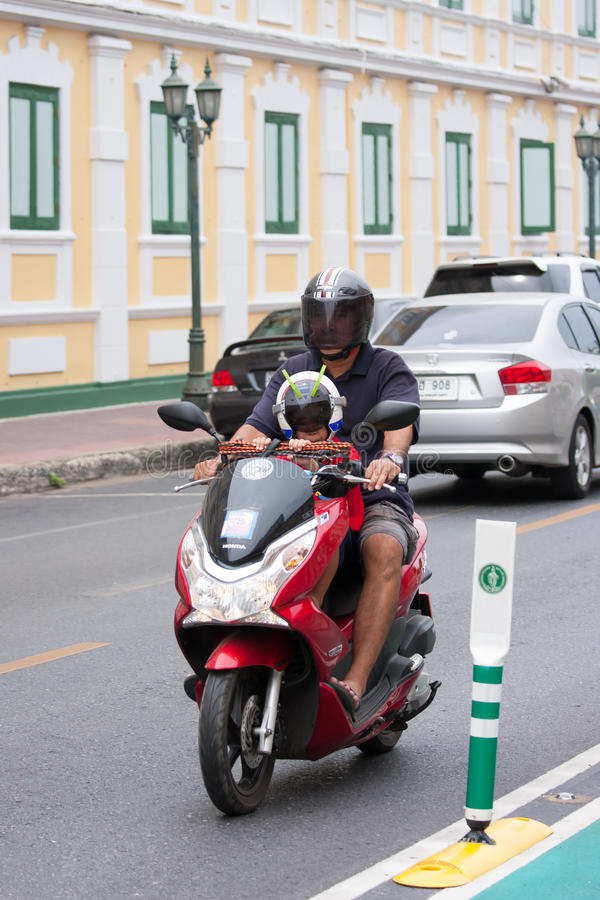 头戴在摩托车的男孩特级英雄盔甲,曼谷 免版税库存图片