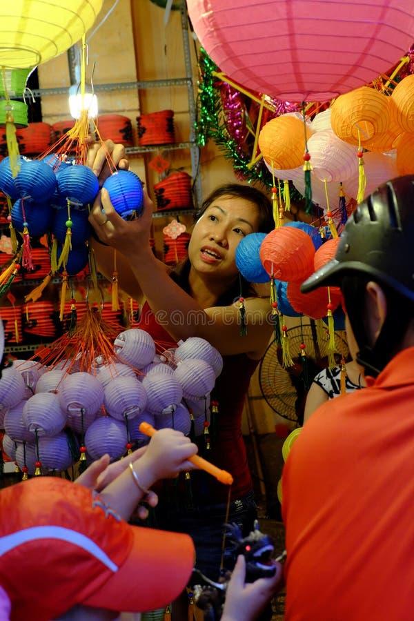 在摩托车购物的中间秋天玩具的越南家庭在夜灯笼街道 库存照片