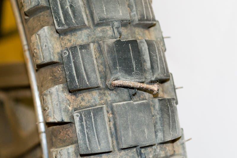 在摩托车轮胎的生锈的钉子 图库摄影