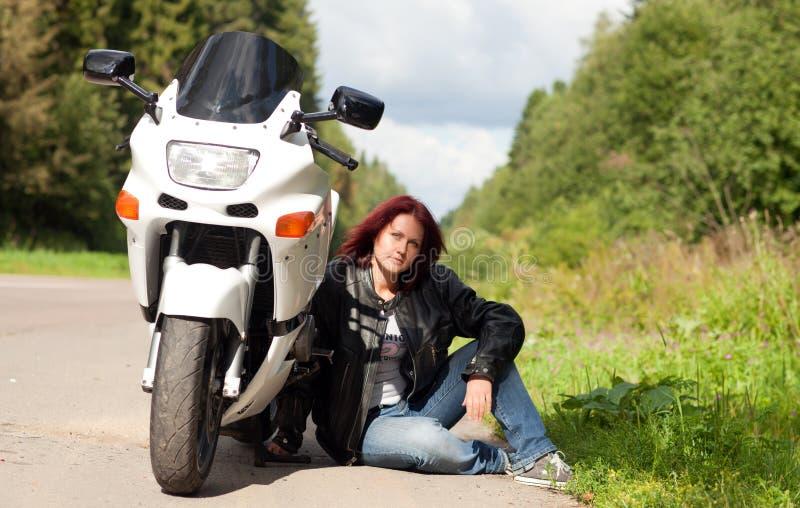 在摩托车附近的妇女 免版税库存照片
