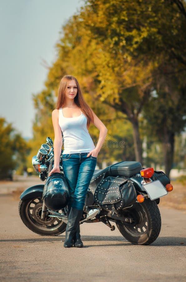 在摩托车附近的美丽的女孩 免版税库存图片