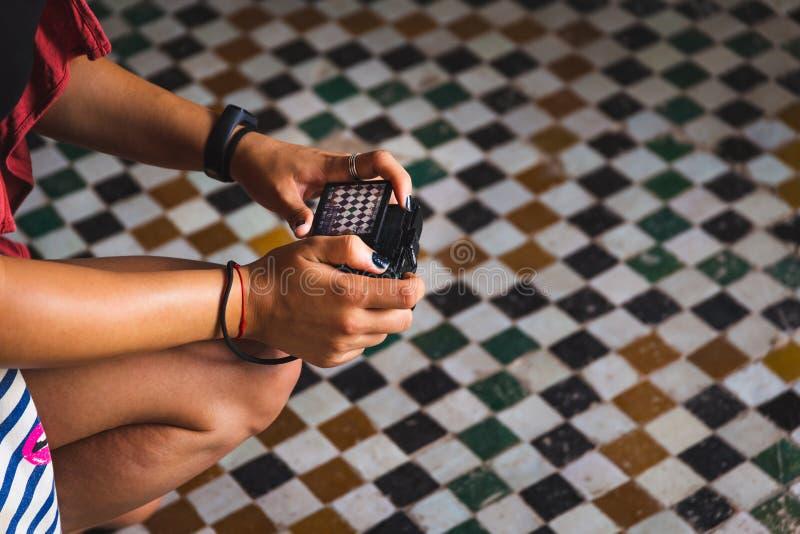 在摩洛哥马拉喀什巴伊亚宫拍照摩洛哥马赛克的年轻妇女 免版税库存照片