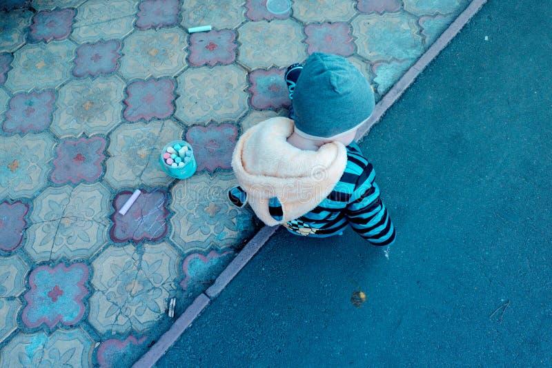 在操场沥青男婴夹克帽子和运动鞋的春日画与不同的蜡笔白垩在瓦片图画的 图库摄影