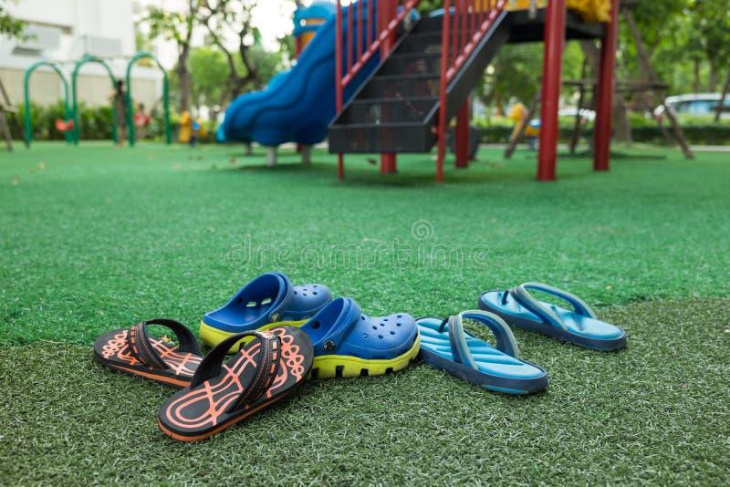 在操场的五颜六色的儿童凉鞋由人为草制成 免版税库存图片