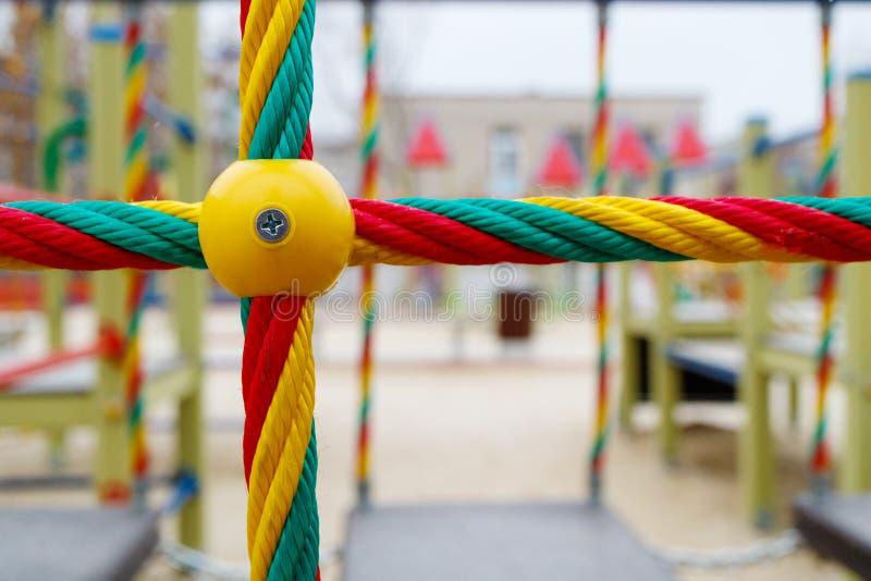在操场的多彩多姿的绳索演奏的孩子,操刀儿童` s室外区域 免版税库存照片