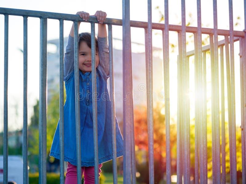 在操场的小女孩戏剧日落的 库存照片