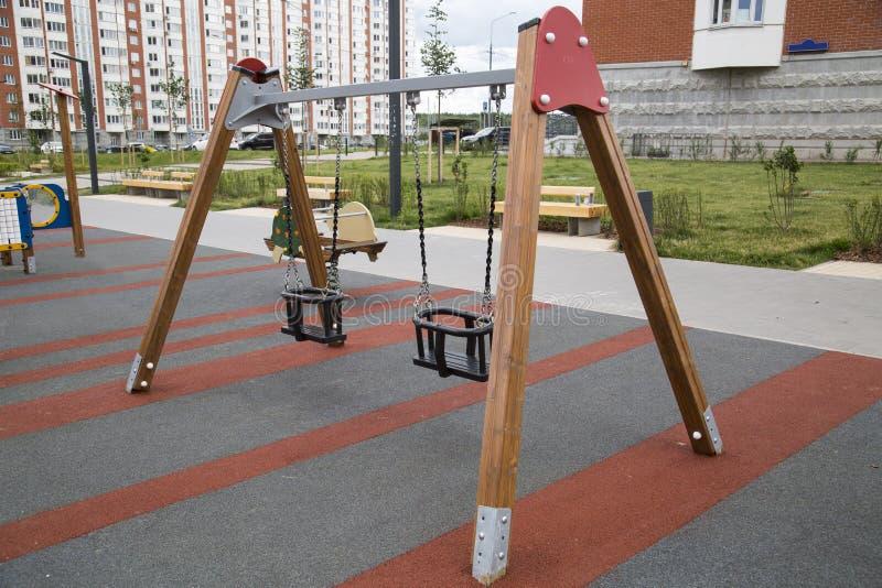 在操场的摇摆儿童的木制支撑在户外城市 免版税库存图片
