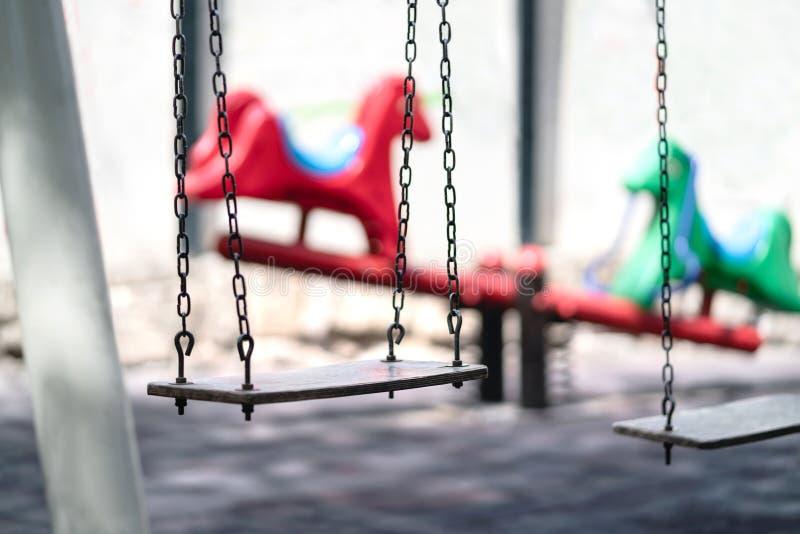 在操场的空的摇摆 消极题材的哀伤的剧烈的心情例如胁迫在学校,虐待儿童,恋童癖 免版税库存照片