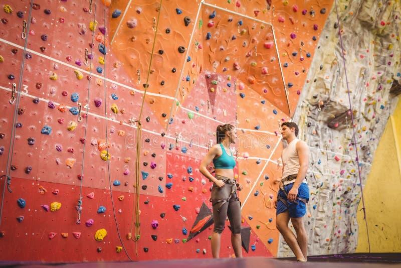 在攀岩墙壁的适合的夫妇 免版税库存照片