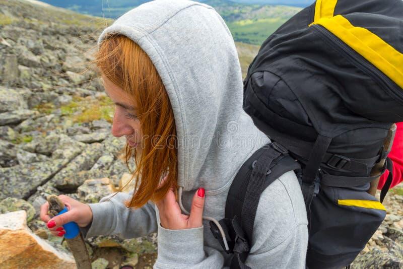在攀登期间的年轻红发女孩登山人山机智 免版税图库摄影