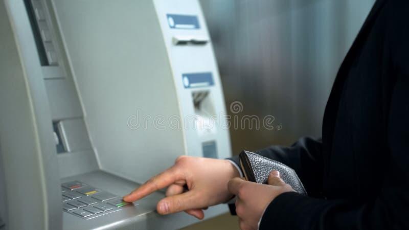 在收到金钱的自动出纳机的商人输入的别针代码 免版税库存照片