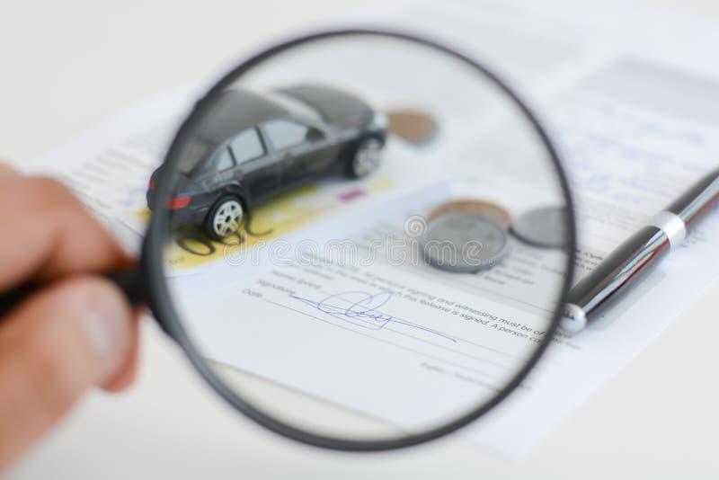 在放大镜下的汽车模型在建议妇女的手上汽车查寻 免版税库存图片