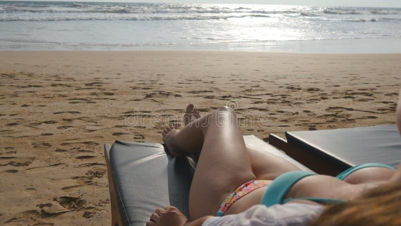 在放松和享用在空的含沙海洋海滩的暑假时的躺椅的女性身体 位于的妇女年轻人 免版税图库摄影