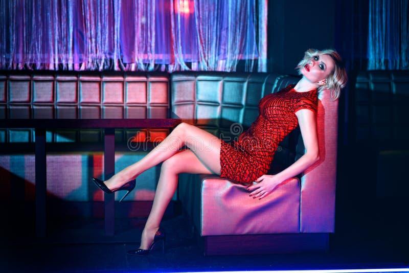 在放松在夜总会的方形的沙发的红色短的适合的衣服饰物之小金属片礼服的美好的白肤金发的模型 免版税图库摄影
