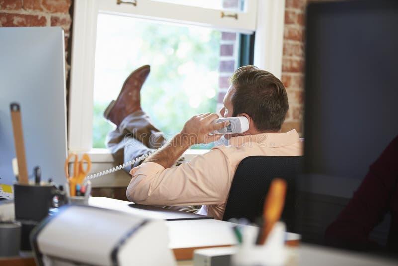 在放松在现代创造性的办公室的电话的商人 免版税库存图片