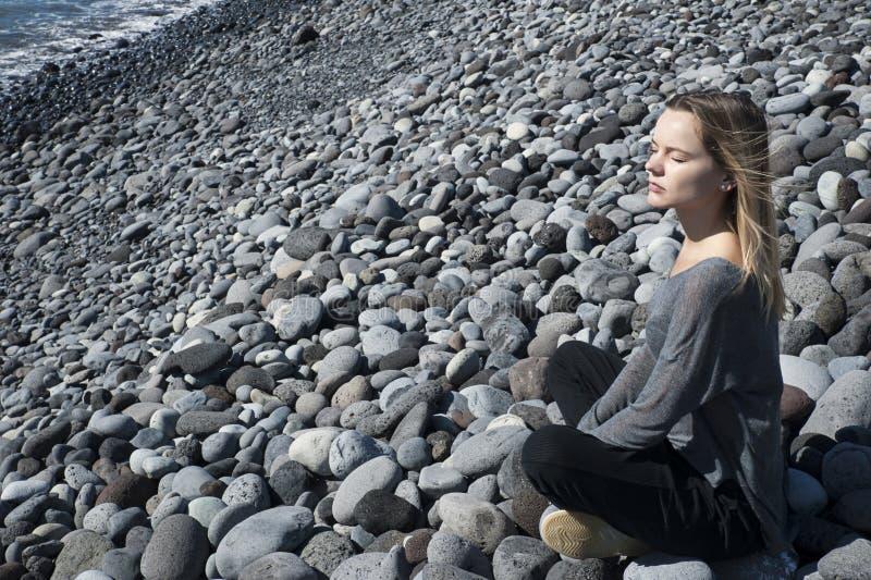 在放松的年轻白肤金发的白种人女性开会,与闭上的眼睛的思考的位置,穿在海滩的中立服装 免版税库存照片