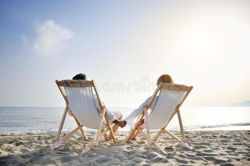 在放松的deckchair的浪漫夫妇享受在海滩的日落 库存图片