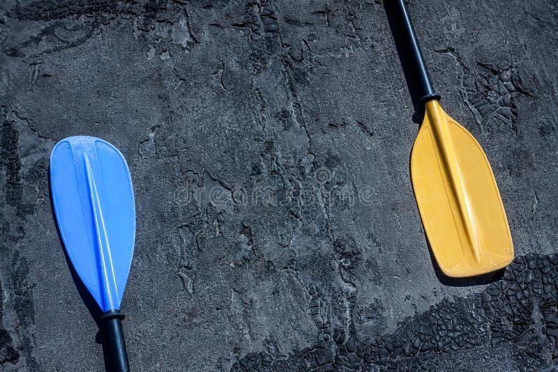 在放置在左右边的灰色织地不很细背景的蓝色和黄色桨 免版税库存照片