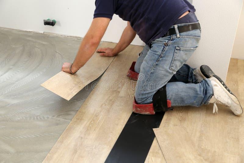 在放置地板的工作 安装新的乙烯基砖地的工作者 库存图片