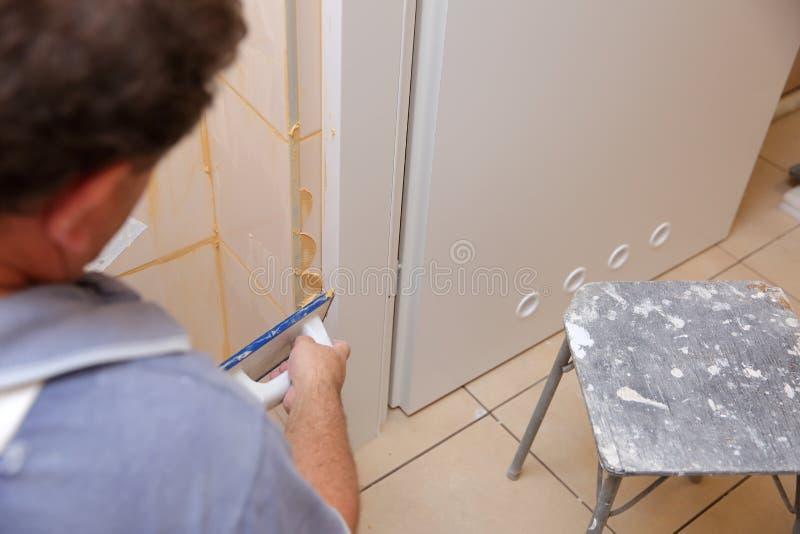 在放置瓦片以后在墙壁,您必须填装在瓦片、特别水泥大量或者赋格曲之间的空间 库存照片