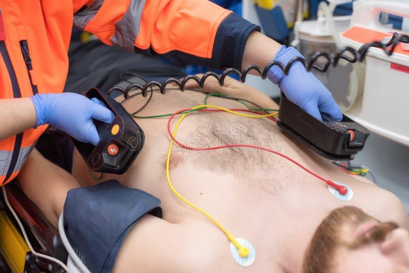 在救护车的医疗紧急 使用去纤颤器的紧急医生 免版税库存图片