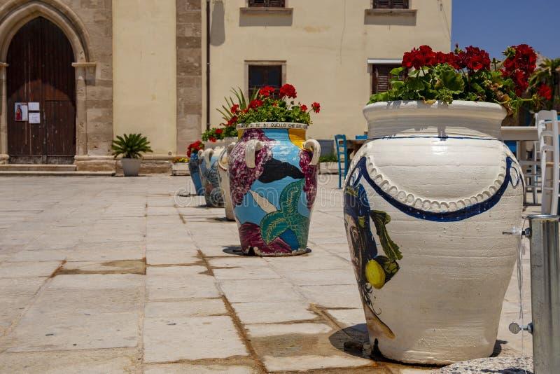 在教会前面被安置的罐五颜六色的花 免版税库存图片