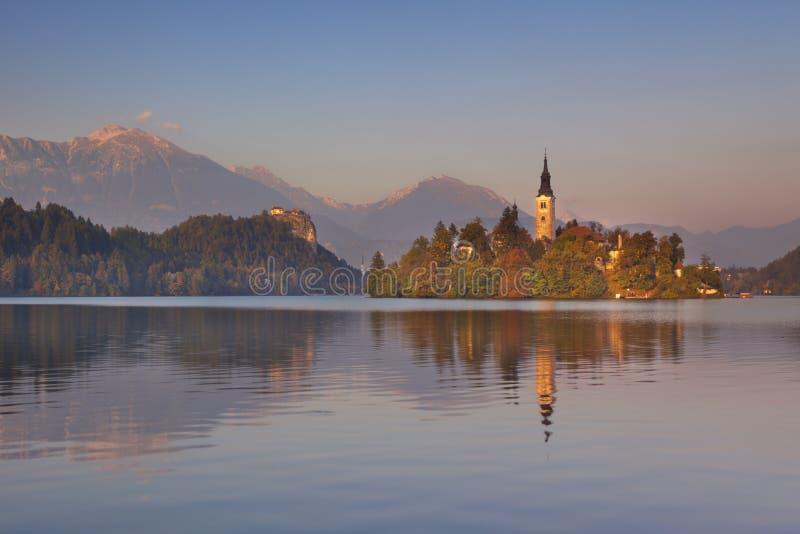 在教会和湖的日落流血的,斯洛文尼亚 免版税库存图片