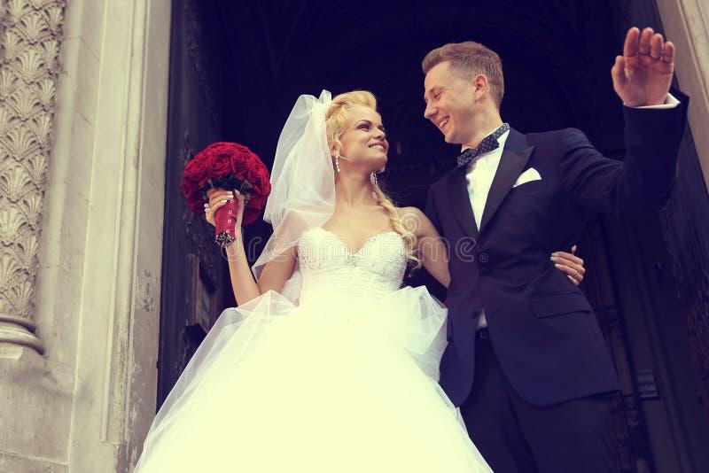 在教会的美好的新娘和新郎仪式有红色玫瑰的开花花束 库存图片