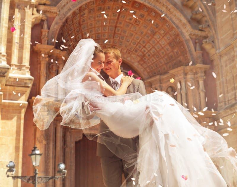 在教会附近的新郎运载的新娘 库存图片