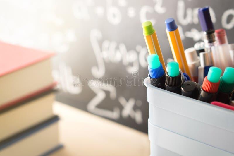 在教室写作持有人和书在黑板前面 免版税库存图片