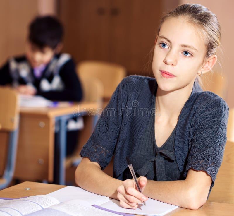 坐在他们的书桌的学校女孩 图库摄影
