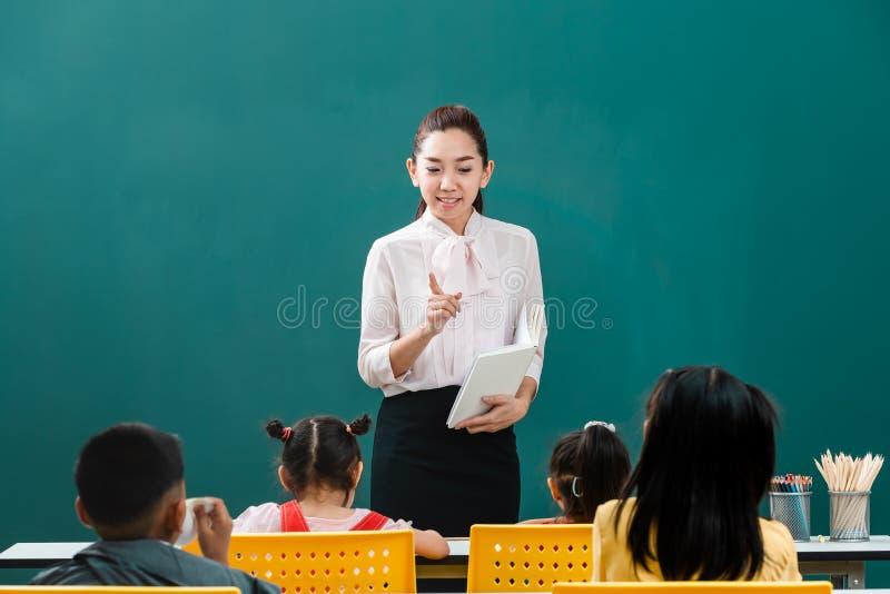 在教室,亚裔老师教学生 免版税图库摄影