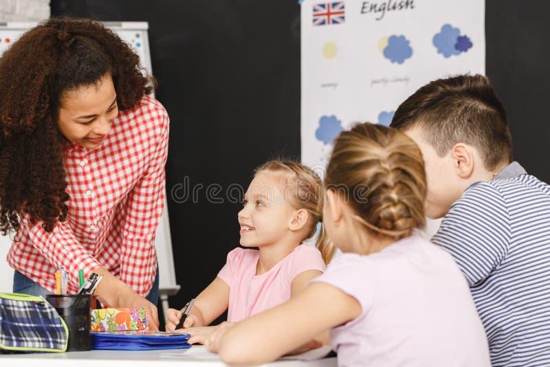 在教训期间的老师帮助的孩子 免版税图库摄影